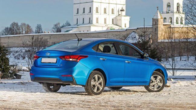 Корейский автомобиль Хёндай Солярис в синем цвете на белом снегу