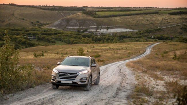 Подъём в гору по грунтовой дороге на автомобиле Хёндай Туссан 2019 года в сером кузове