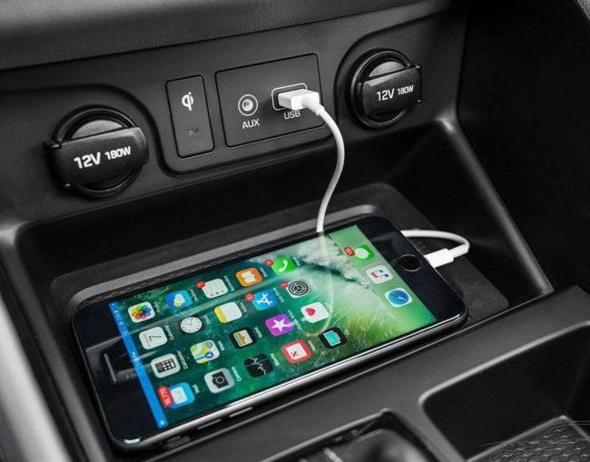 Смартфон на беспроводной зарядке в салоне автомобиля Хёндай Туссан 2019 года выпуска