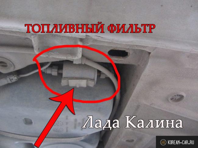 Топливный фильтр под днищем автомобиля рядом с бензобаком Лада Калина