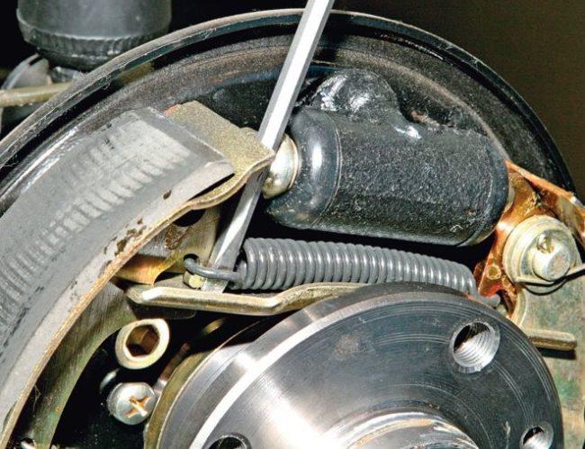 Снятие верхней пружины с тормозной колодки заднего колеса на Лада Калина