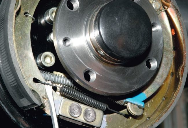 Снятие нижней пружины с тормозных колодок в заднем колесе седана Калина
