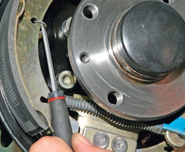 Снятие отверткой прижимной пружины с тормозной колодки на Лада Калина