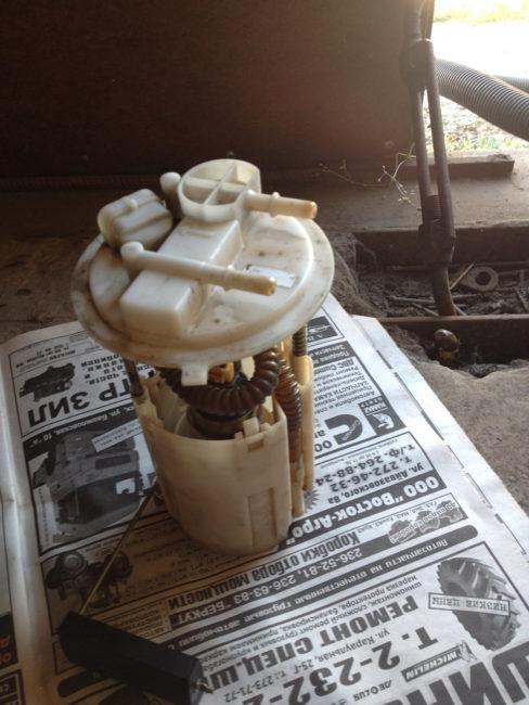 Топливный насос из автомобиля Лада Калина на старой газете