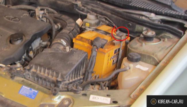 Минусовая клемма аккумулятора под капотом автомобиля Лада Калина