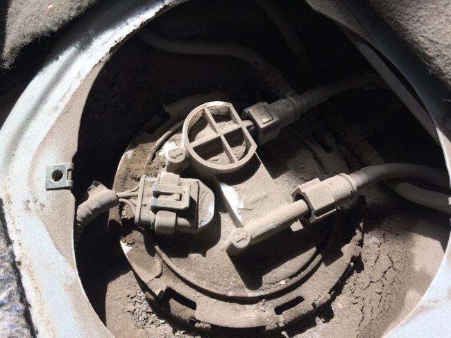 Запыленная крышка топливного насоса на бензобаке автомобиля Лада Калина