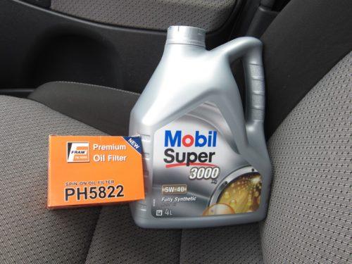 Пластиковая канистра с маслом Mobil Super 5W-40 на водительском сидении в Лада Калина