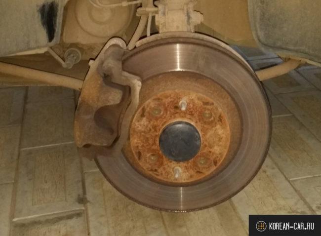 Передние тормозные колодки и тормозной диск на Лада Калина вблизи