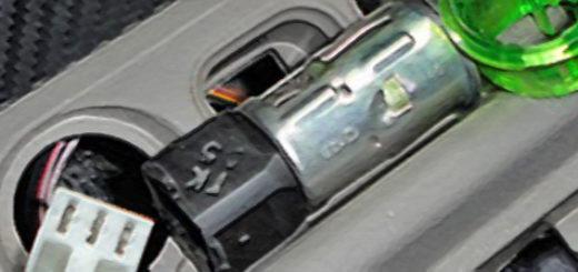 Демонтированный прикуриватель с Лада Калина лежит на панели