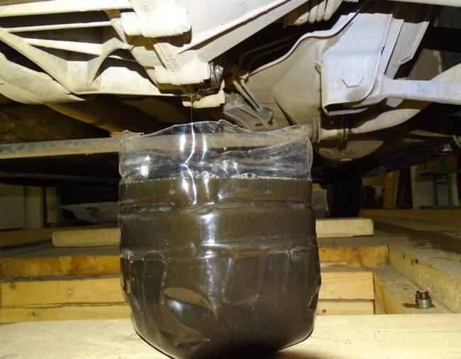 Старое отработанное масло из механической КПП автомобиля Лада Калина