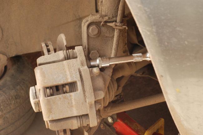 Выворачивание болта суппорта в передних тормозах Лада Калины