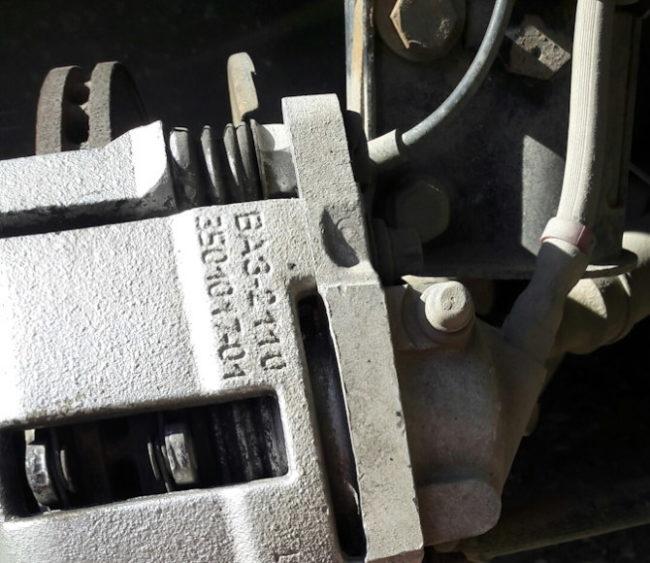 Смотровое окошко на скобе суппорта передних тормозов в Лада Калине