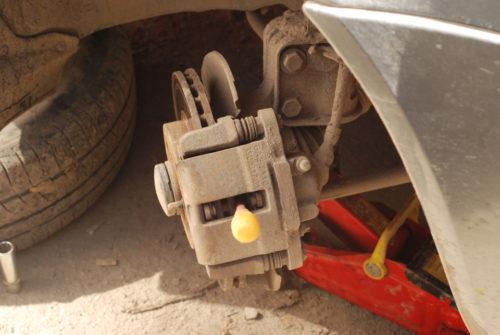 Отжатие плоской отверткой тормозного цилиндра в переднем колесе Лада Калины