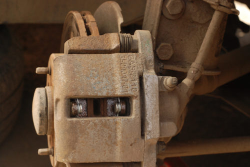 Усики пружинок на передних колодках в смотровом окошке переднего колеса Лада Калины